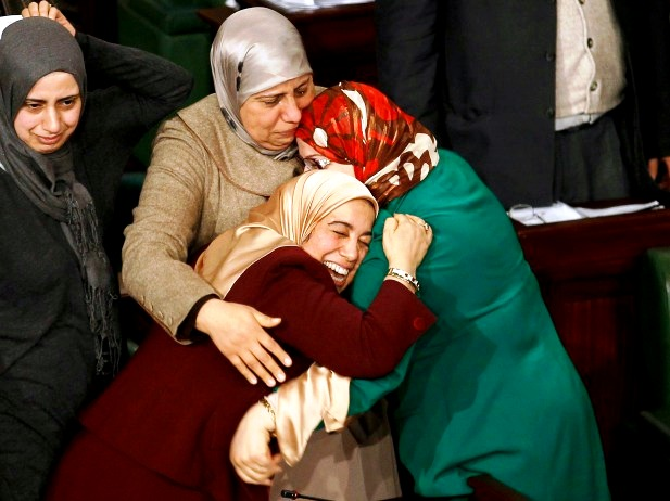 of the Tunisian parliament celebrate after approving the country