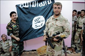 Peshmerga fighters pose in front of an Islamic State flag they took from militants at a military post about 30 kilometres north of Kirkuk, on September 13, 2014. Photo: AFP/Guillaume Briquet